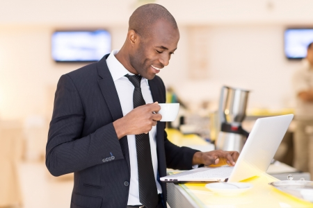 african ethnicity: Business on the go. Cheerful young African man in formalwear using his laptop while standing at the bar
