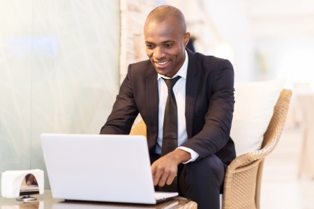 Business on the go. Cheerful young African businessman using his laptop while sitting at the restaurant  Stock Photo - 24487816
