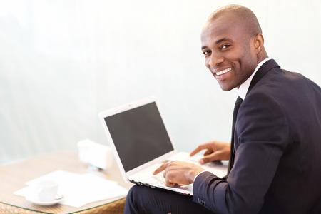 business smile: Hombre de negocios con ordenador port�til. Hombre de negocios africano joven alegre escribir algo en la computadora port�til y mirando por encima del hombro