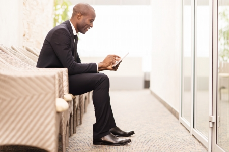 adult man: Checking his schedule on the go. Side view of cheerful young African businessman working on digital tablet while sitting on the chair