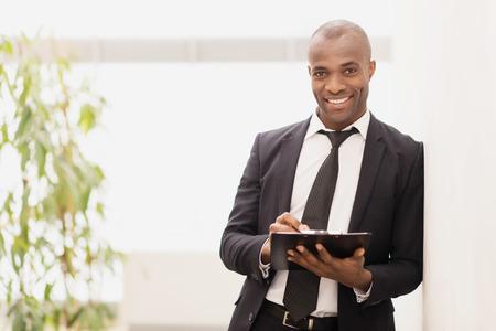 Uomo d'affari con il rilievo di nota. Allegro giovane imprenditore africano scrivendo qualcosa nel suo taccuino e sorridere alla telecamera Archivio Fotografico - 24481585