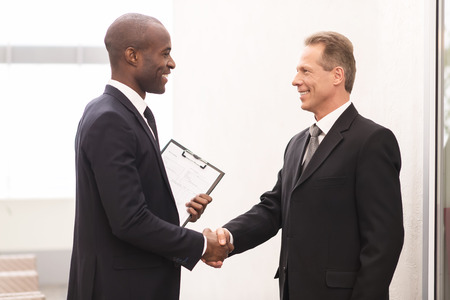 Business meeting. Two cheerful business men shaking hands and looking at each other