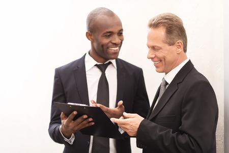dos personas hablando: Hablar de un nuevo proyecto. Dos hombres de negocios alegres que miran el bloc de notas y haciendo gestos