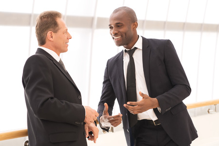 two people talking: Business communication. Two cheerful business men talking to each other and gesturing Stock Photo