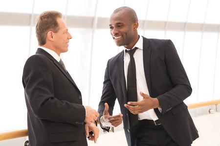 dos personas conversando: La comunicación empresarial. Dos hombres de negocios alegres que hablan el uno al otro y que gesticulan