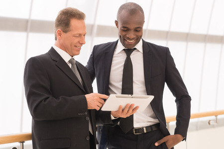 Discussing a new project. Two cheerful business men looking at the digital tablet and smiling photo