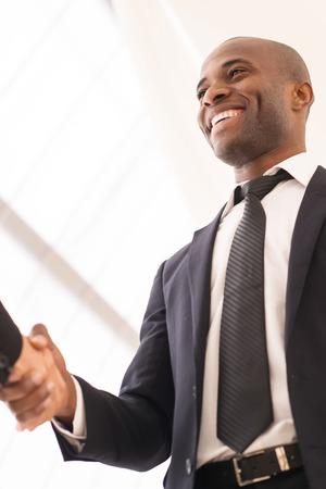 buen trato: Buen trato. Primer plano de bajo �ngulo de visi�n de los hombres de negocios apret�n de manos Foto de archivo