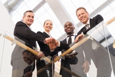 empleado de oficina: Equipo de negocios fuerte. Bajo el ángulo de cuatro hombres de negocios seguros de pie cerca uno del otro y tomados de la mano juntos