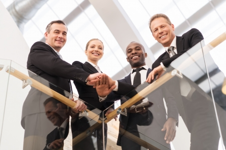 business relationship: Strong business team. Low angle view of four confident business people standing close to each other and holding hands together