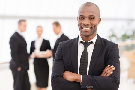 hombre de negocios: Hombre de negocios confidente. Hombre africano joven alegre en ropa formal manteniendo los brazos cruzados y sonriendo mientras sus colegas de pie en el fondo