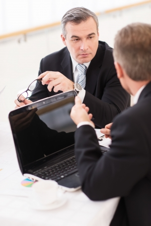 business man laptop: Business meeting. Business people in formalwear discussing something while sitting together at the table