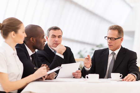 business attire: Business meeting. Business people in formalwear discussing something while sitting together at the table