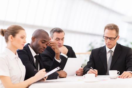 gente sentada: La gente de negocios cansado. Cuatro hombres de negocios en ropa formal con aspecto cansado mientras est� sentado junto a la mesa Foto de archivo