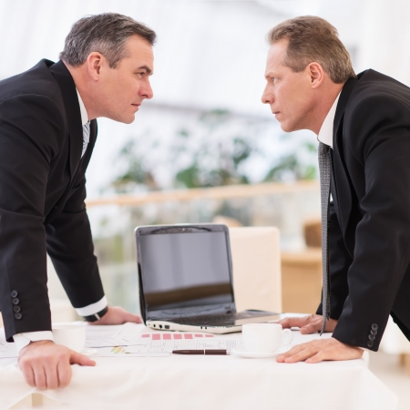 two face: Business confrontation. Two mature men in formalwear conflicting while standing face to face Stock Photo