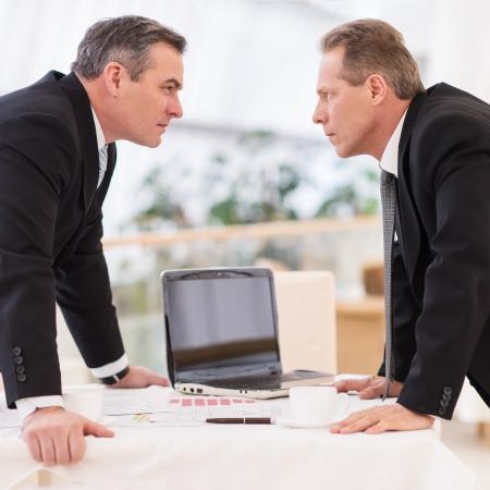 dos personas platicando: Confrontación del asunto. Dos hombres maduros en ropa formal en conflicto mientras está de pie frente a frente Foto de archivo