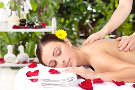 Spa girl. Beautiful young woman with flower in head lying on front while massage therapist massaging her back photo