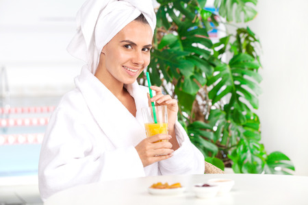 Woman at spa. Beautiful young woman in bathrobe drinking juice while sitting in front of swimming pool photo