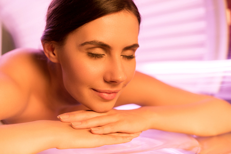 naked body: Solarium treatment. Close-up of attractive young woman lying on tanning bed and smiling
