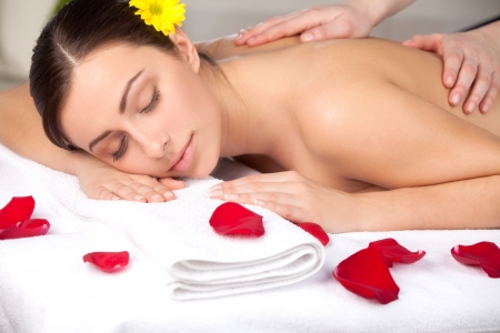 Total relaxation. Attractive young woman with flower in head lying on front while massage therapist massaging her back photo
