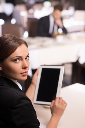 Businesswoman with digital tablet. Rear view of beautiful young woman in formalwear working on digital tablet and looking over shoulder while sitting at the restaurant photo