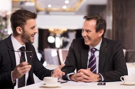job satisfaction: Great success. Two cheerful business people in formalwear discussing something and smiling while sitting at the restaurant