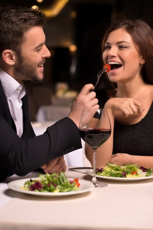 It is delicious! Beautiful young couple feeding each other and smiling while spending time at the restaurant photo