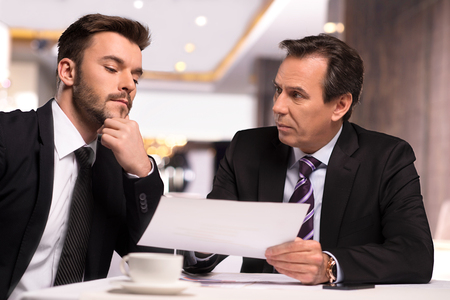 discussing: Discussing contract. Two business people in formalwear discussing something while one of them showing a paper to another one Stock Photo