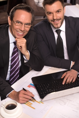 mature businessman: Business people. Top view of two business people in formalwear smiling at camera while working on laptop