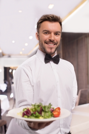 Cheerful waiter. Handsome young waiter in shirt and bow tie holding a plate with salad and smiling 版權商用圖片