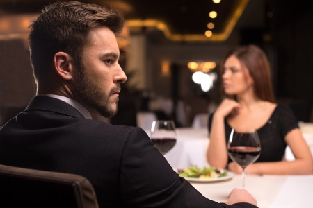 No more words. Thoughtful young couple sitting at the restaurant and looking away photo