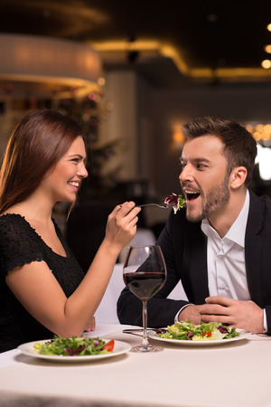 Try it! Beautiful young couple feeding each other and smiling while spending time at the restaurant photo