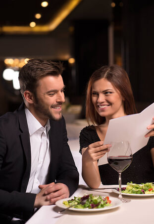 She knows what she wants. Beautiful young looking at the menu and smiling while sitting at the restaurant photo