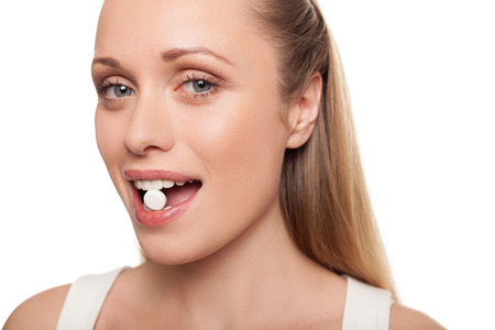 taking pill: Pill in her mouth. Portrait of young woman holding pill in her mouth and smiling while isolated on white  Stock Photo
