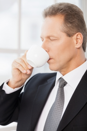mature businessman: Morning coffee. Side view of mature man in formalwear drinking coffee and keeping eyes closed