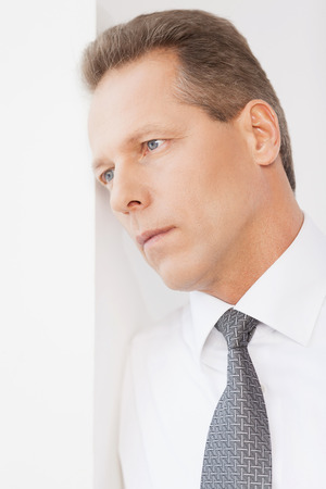 Waiting for inspiration. Thoughtful mature man in shirt and tie leaning at the wall and looking away photo