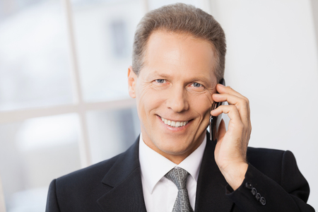 Always in touch. Portrait of cheerful mature man in formalwear talking on the phone and smiling to you while standing near window  photo