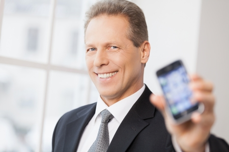 Businessman with mobile phone. Portrait of cheerful senior man in shirt and tie showing his mobile phone to camera and smiling  photo