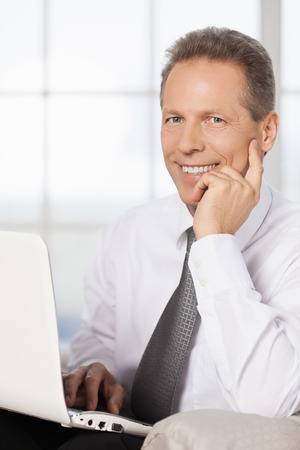 mature businessman: Businessman with laptop. Cheerful mature man in shirt and tie using computer and holding hand on chin