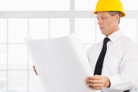 Architect at work. Confident senior man in formalwear and hardhat holding a blueprint and looking at it