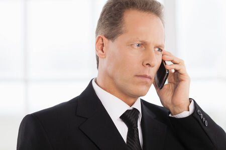 mature businessman: Businessman on the phone. Portrait of confident mature man in formalwear talking on the phone while standing near window  Stock Photo