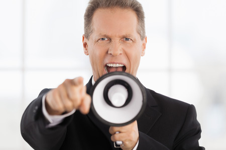 Yes, You! Portrait of confident mature man in formalwear shouting at megaphone and pointing camera photo