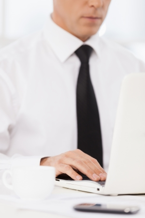 Businessman at work. Cropped image of confident mature man in shirt and tie using computer while sitting at his working place photo