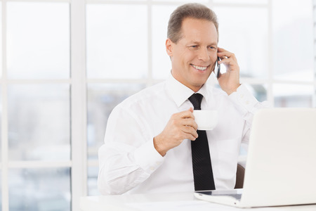 one senior man only: He is always in touch. Cheerful mature man in formalwear drinking coffee and talking on the mobile phone while sitting at his working place Stock Photo