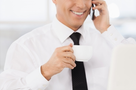 Cheerful businessman. Cropped image of smiling mature man in formalwear drinking coffee and talking on the mobile phone while sitting at his working place photo