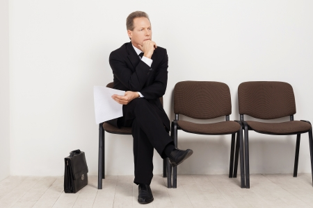 keeping room: Job candidate. Bored mature man in formalwear holding paper and keeping legs crossed at knee while sitting at the chair in waiting room Stock Photo