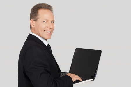 over the shoulder view: Businessman with laptop. Rear view of senior man in formalwear typing something on laptop and looking over shoulder while standing against grey background