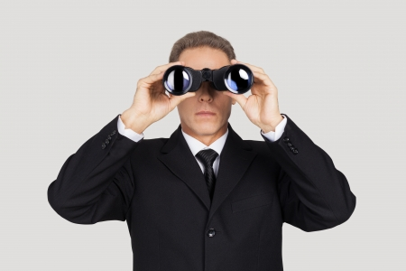Looking for the new opportunities. Confident mature man in formalwear looking through binoculars while standing against grey background  photo