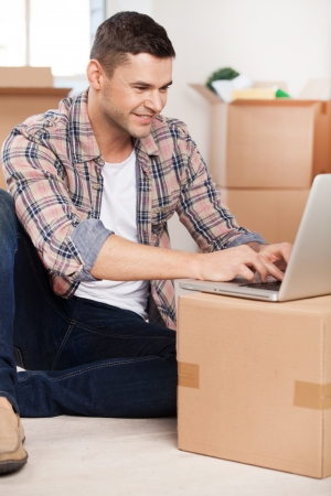 surfing the web: Surfing web in a new house. Handsome young man sitting on the floor and typing something on laptop while cardboard boxes laying on the background