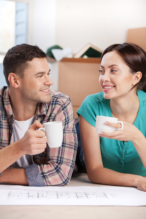 Planning a house improvement. Cheerful young couple lying on the floor and drinking coffee while cardboard boxes laying on the background  photo