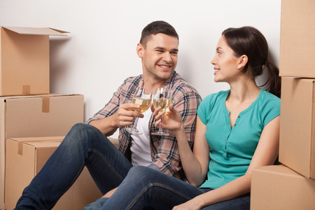 Celebrating their moving to a new apartment. Cheerful young couple sitting on the floor and drinking wine while cardboard boxes laying around them  photo